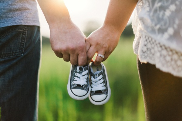 Image by Free-Photos from Pixabay Man and woman holding hands and a pair of baby shoes between them